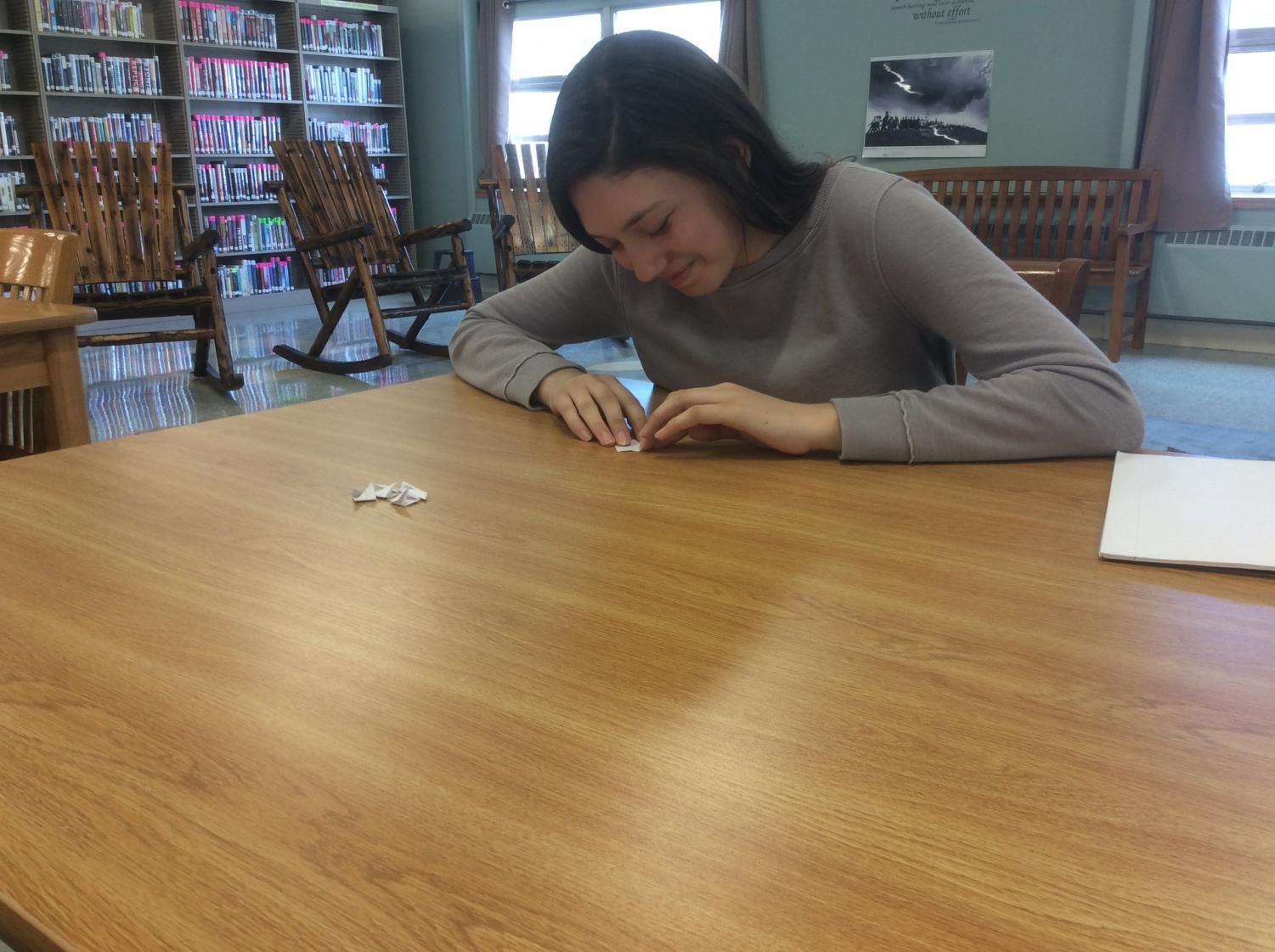 Kylee Plummer '21, makes origami in the PIHS library.