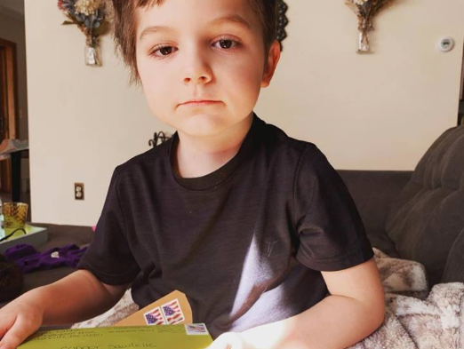 "Six year-old Connor Sawtelle of Augusta sits with some of the cards of encouragement people have sent. Connor has received over 1,000 cards, according to his mother, Erika Sawtelle. ""I am so thankful for our community and everyone who has sent a card,"" she said. ""We are slowly working our way through the huge pile. But I cherish every card sent!"""
