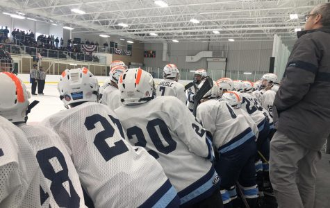 Wildcat hockey players discuss strategy in a timeout during the inaugural preseason tournament at PCIA. Players added orange tape to their helmets in recognition of recently deceased Brewer hockey player, Jordan Parkhurst.
