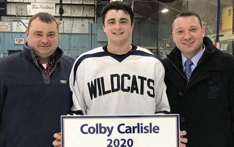 Junior Colby Carlisle poses with his father and uncle following his 100th point on January 25th at the Northern Maine Forum in Presque Isle
