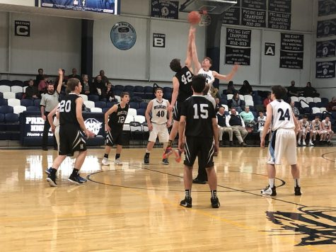 "A JV boys basketball game between Presque Isle and Houlton tips off on December 11th of 2019. This season, given the undoing pandemic, the MPA has decided to eliminate the tip off in favor of a coin toss to decide possession. ""It's going to be so different doing a coin toss,"" said senior Hattie Bubar. ""I feel like it's not the same without a tip off."