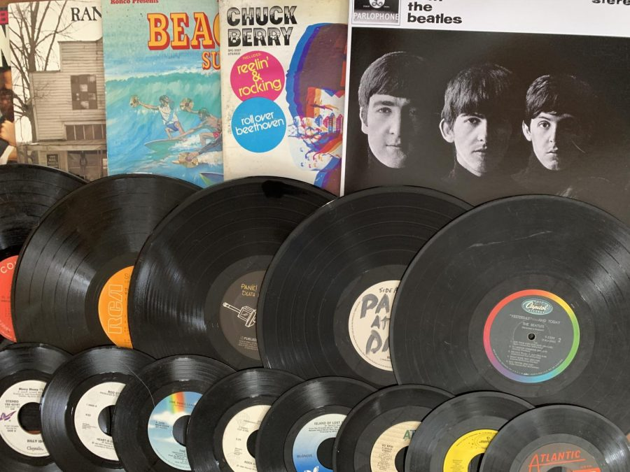 Record discs, as well as old record covers, are laid out across a table.