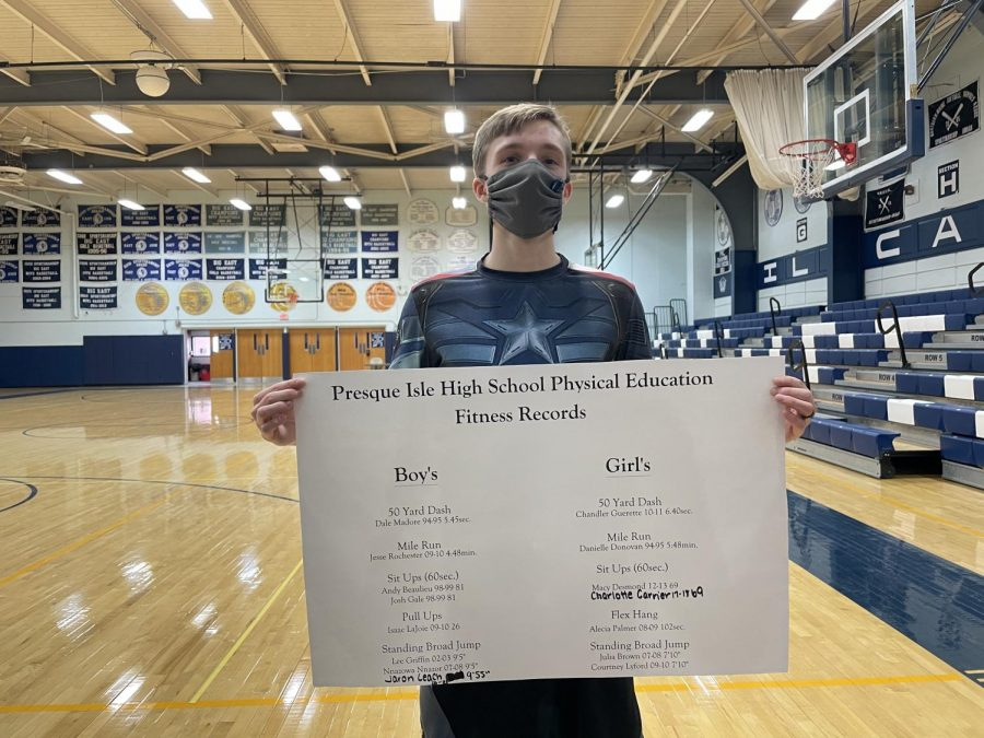 Jaron Leach '22, poses with the fitness records sheet after tying the record for the standing broad jump Monday, January 25.